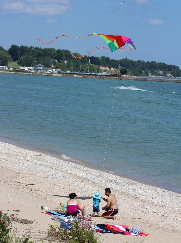 family-on-crescent-beach-flying-kite